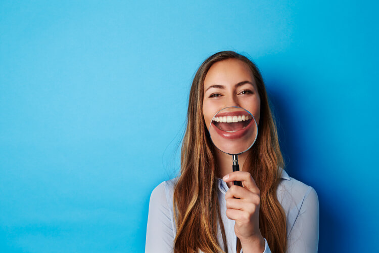 Brunette woman smiles as she holds a magnifying glass up to her teeth against a blue wall