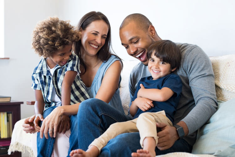 Multiracial family of mom, dad, and two sons smile and laugh while sitting on a couch