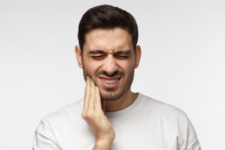 Dark-haired man cringes in pain and touches his cheek due to a toothache